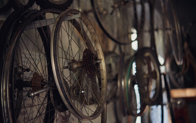 Detail of old bicycle wheel rim hanging in abandoned workshop
