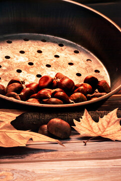 Autumn vibes: Chestnuts in the pan on a wooden background