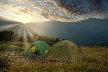 view of tourist tent in mountains at sunrise or sunset. Camping background. Adventure travel active lifestyle freedom concept. Summer vacation