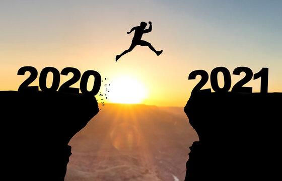 Mann spring über Abgrund vor Sonnenuntergang mit der Beschriftung 2020/2021.
