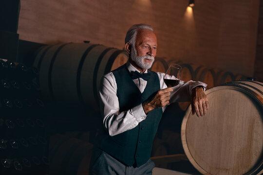 Elderly rich man savoring red wine in his wine cellar