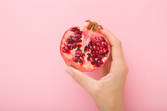Young adult woman hand holding half of pomegranate on light pink table background. Pastel color. Closeup. Fresh fruit. Top down view.