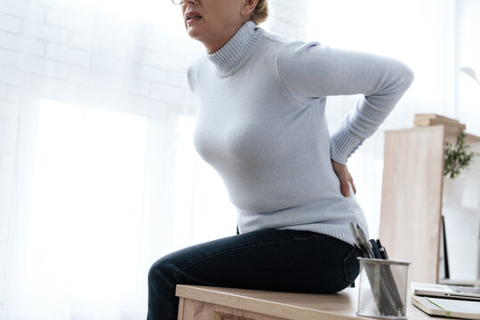 Woman sitting and suffering from severe back pain.