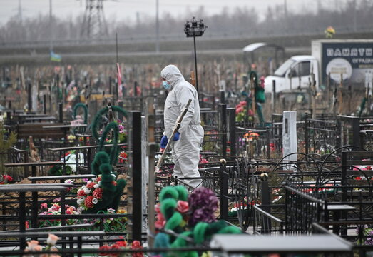 A grave digger is seen at a cemetery during the funeral of a person, who presumably died of the coronavirus disease (COVID-19), in Omsk