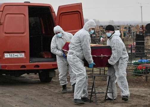 Grave diggers move the coffin of a person, who presumably died of the coronavirus disease (COVID-19), during a funeral in Omsk