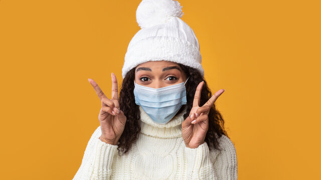 Portrait of black woman in medical mask showing victory sign