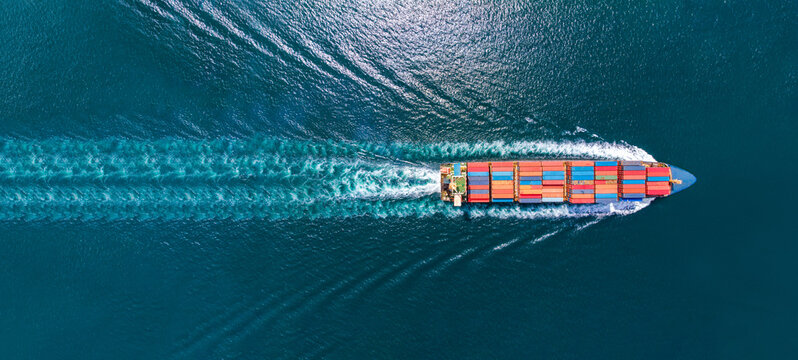 Aerial top view of cargo ship with contrail in the ocean sea ship carrying container and running for export from container international port to custom ocean concept freight shipping by ship service