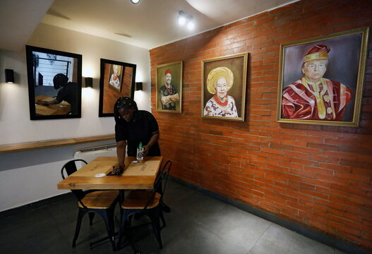 A worker cleans a desk next to paintings including a painted portrait of U.S President Donald Trump wearing a gold-trimmed red agbada, a traditional flowing robe worn by Yoruba men in southern Nigeria, in a upscale restaurant in Lagos