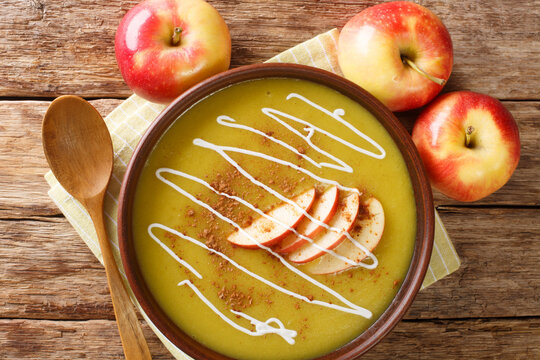 Delicious Austrian apple puree soup with cinnamon close-up in a plate on the table. horizontal top view from above
