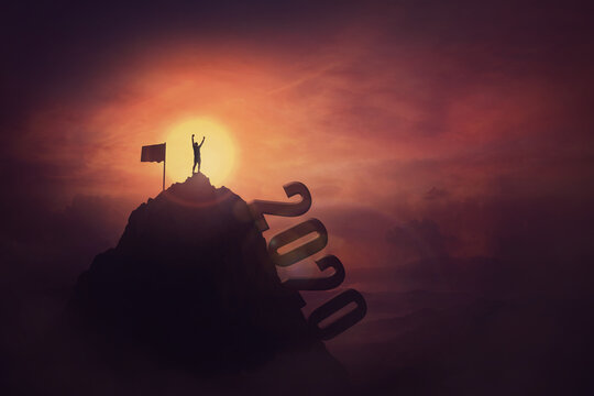 Overcome challenges concept, a courageous man, raising hands up, on the top of the 2020 year mountain, reaching the finish flag, achieving success. Person faced all the obstacles in the past and win.