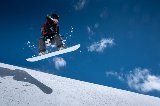 Young woman on a snowboard makes a flight after jumping from a snowy ledge against a dark blue sky high in the mountains in winter