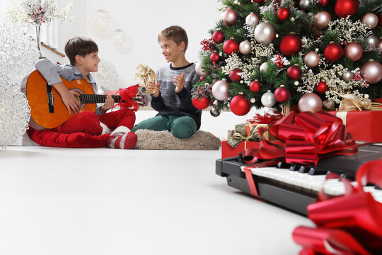merry christmas and happy holidays, children play guitar and tambourine near the christmas tree with wrapped gift packages and musical instruments, at home in the living  room sitting on the floor