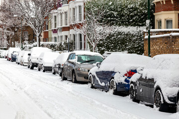 Fototapeta Street winter cityscape with snow terraced houses and frozen cars after a blizzard snowfall in London England UK, stock photo image with copy space