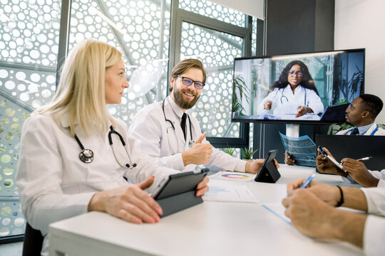 Team of multiethnic physicians, listening lecture of female afro american doctor at medical video conference in the clinic. Focus on handsome bearded Caucasian doctor showing thumb up