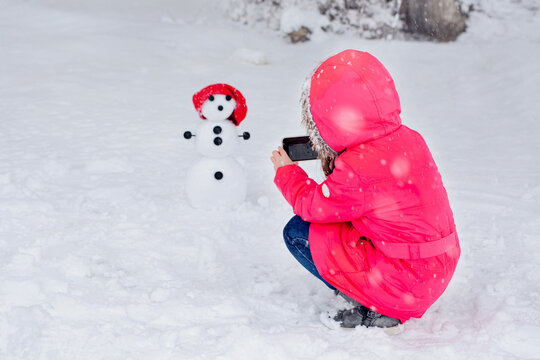 A child photographs a snowman with a phone na outdoors in the forest.