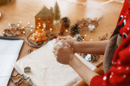 Hands kneading raw gingerbread dough on background of metal cutters on rustic table. Christmas