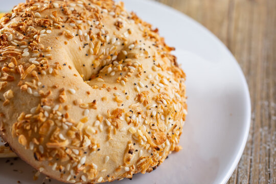 A view of an everything bagel on a plate, in a restaurant or kitchen setting.
