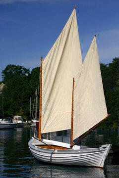 Two masted sailboat in harbor of York, Maine with sails aloft.