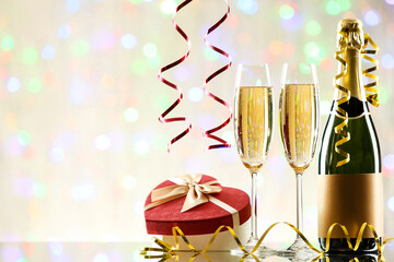 Bottle and glasses of champagne with gift box on blurred lights background