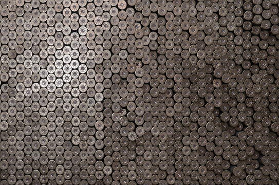 Pattern of 12 gauge cartridges for shotgun bullets. Shells for hunting rifle close up. Backdrop for shooting range or ammunition trade concepts