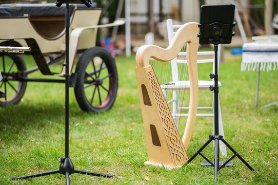 Celtic wooden lap harp on green grass, chair and music stand in backyard without music players