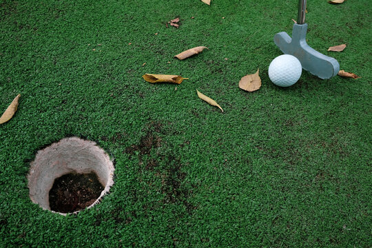 Playing mini golf on artificial green grass outdoors with fallen leaves. Setting goals and winning concept. Fun vacation entertainment for fall. Putting club at ball on golf course. Golfing challenge