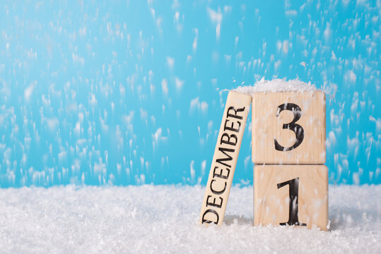 2021 is coming concept. Close up photo of wooden cube calender showing the last day of old year on snow falling background and blue bright color sky background