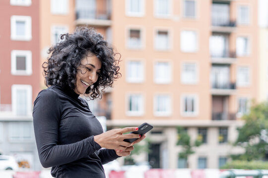 Closeup shot of a Spanish woman smiling while using her phone on a blurred background