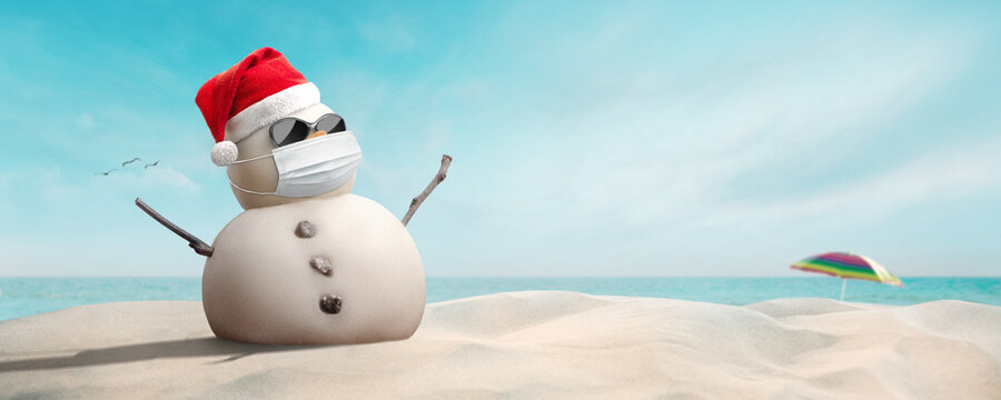 Concept: sand snowman wearing sunglasses, Santa hat and mask during coronavirus pandemic on sunny Christmas day afternoon COVID-19