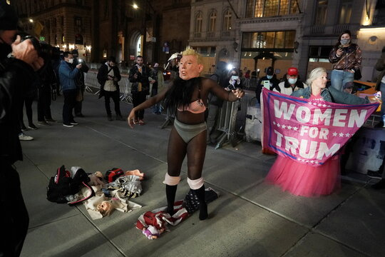 A woman with a U.S. President Donald Trump mask dances on a U.S. flag outside Trump Tower on Election Day in the Manhattan borough of New York City