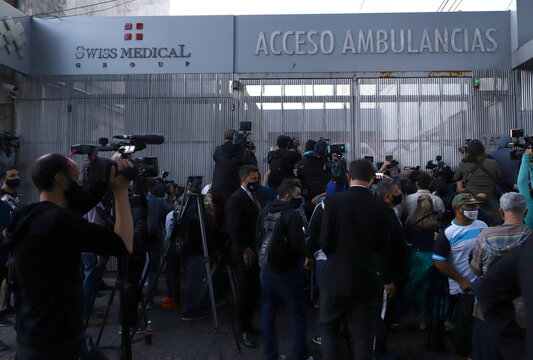 Reporters and fans of Argentine soccer great Diego Maradona gather outside the clinic where he will be undergoing surgery for a subdural haematoma, according to his personal physician, in Olivos