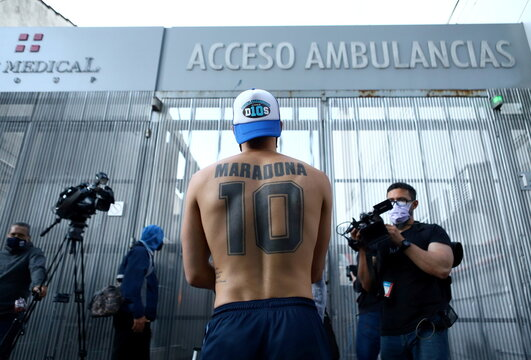 A fan of Argentine soccer great Diego Maradona stands outside the clinic where he will be undergoing surgery for a subdural haematoma, according to his personal physician, in Olivos