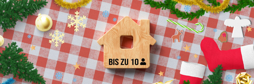 christmas decoration on kitchen table background and wooden house symbol with German message for UP TO 10 PERSONS as a hint to German Corona regulations