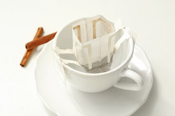 Drip coffee bag in cup on white table, closeup