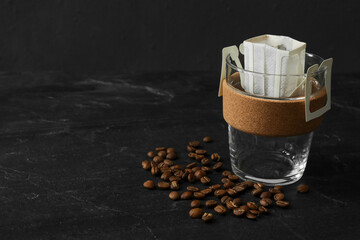 Glass cup with drip coffee bag and beans on black slate table, closeup. Space for text