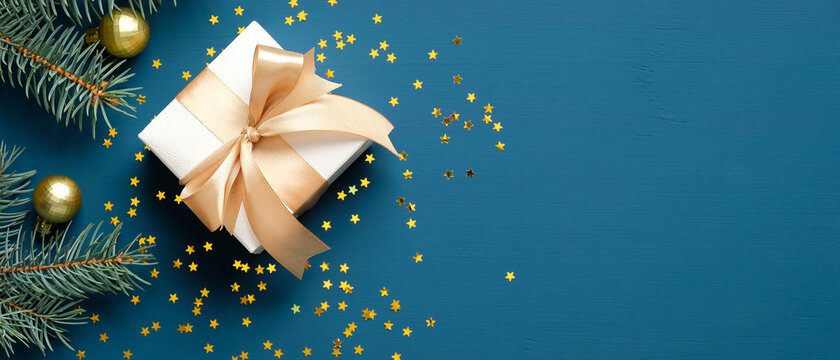 Christmas gift box with golden ribbon bow, fir branches, confetti on dark blue background. Xmas banner design, header mockup. Flat lay, top view, copy space.