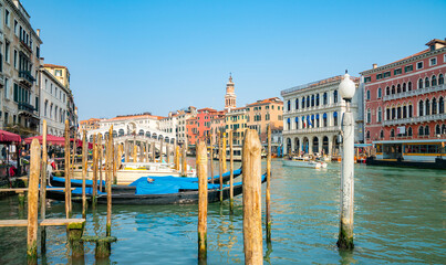 Beautiful view of traditional Gondola on famous Canal Grande with Rialto Bridge at daytime