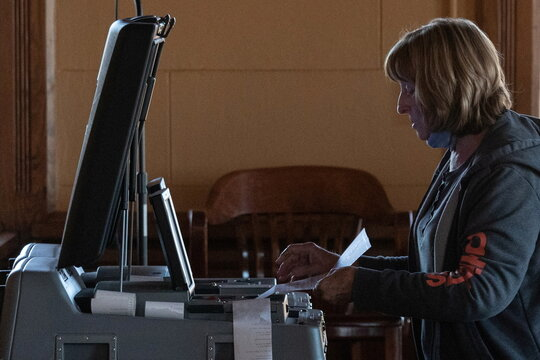 An election official scans a mail in ballot while tallying votes for the 2020 U.S. presidential election in Marfa, Texas
