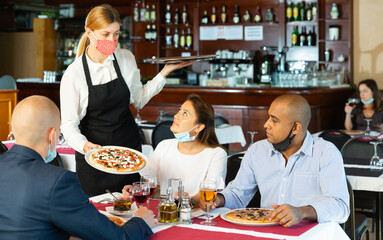 Hospitable waitress wearing face protective mask bringing ordered pizza to guests. New normal restaurant concept in coronavirus pandemic ..