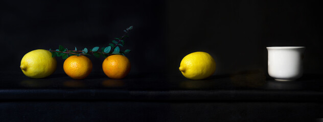 orange and lemon fruit for food with white ceramic drink cup classic still life on black background