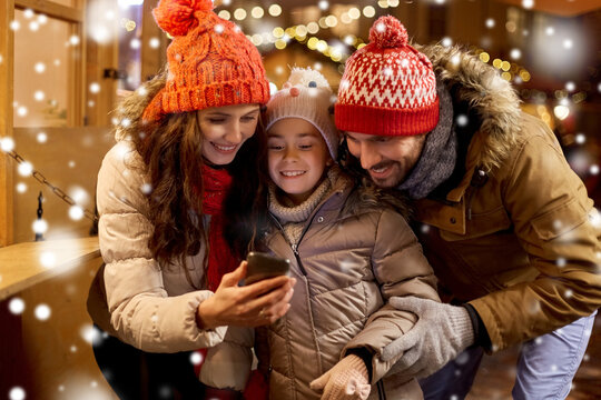 family, winter holidays and technology concept - happy mother, father and little daughter with smartphone at christmas market in evening over snow