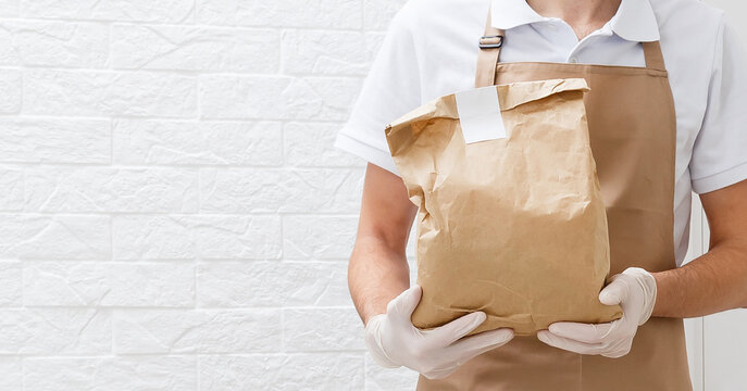 Holding take-out food paper bag, coffee cup. Light grey background, place to insert your text. Delivery man.