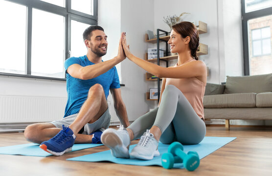 sport, fitness, lifestyle and people concept - smiling man tying laces and woman making high five at home