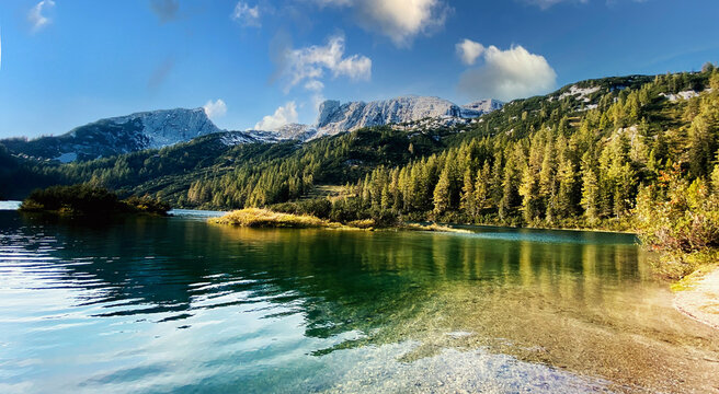 Wonderful vacations on the region Salzkammergut in Austria, Eur; hiking on the waterside  of the six lakes on the Tauplitz-Alm (alpine pasture); panoramic view with hills and reflections on the water.