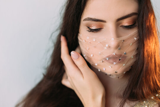 Covid-19 beauty. Festive accessory. Quarantine party style. Portrait of tender brunette woman with evening makeup in glamour transparent face mask isolated on light neutral background.