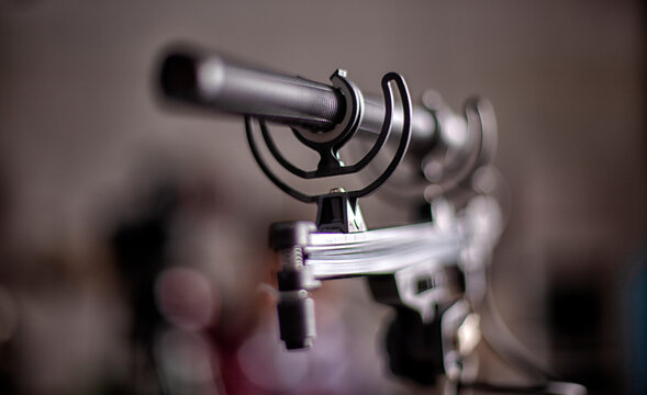 Shotgun microphone. Condenser hypercardioid mic mounted on stand with cable attached. Macro shot .