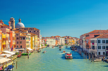 Venice cityscape with Grand Canal waterway. View from Scalzi bridge. Gondolas, boats, yachts, vaporettos docked and sailing Canal Grande. Venetian architecture buildings. Veneto Region, Italy.