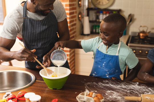 African american father and son wearing apron baking in the kitchen at home