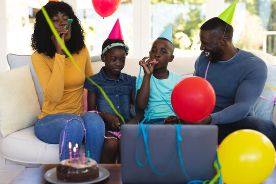 african american family wearing party hats celebrating birthday and blowing party blowers while sit