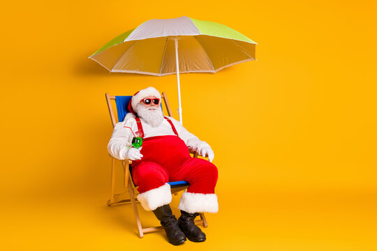 Full body photo of grey white hair bearded santa claus chill chaise-lounge hold cocktail x-mas christmas eve noel time rest wear hat pants boots isolated bright shine color background